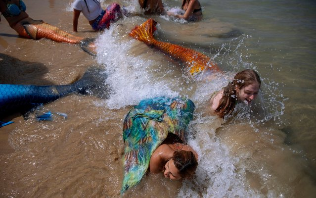 Members of the Israeli Mermaids Community bathe in the sea with a mermaid tails at the beachfront in Bat Yam, near Tel Aviv, Israel, Saturday, May 23, 2020. Members of the Israeli mermaid community gathered at the beachfront to mark the beginning of the bathing season. (Photo by Oded Balilty/AP Photo)