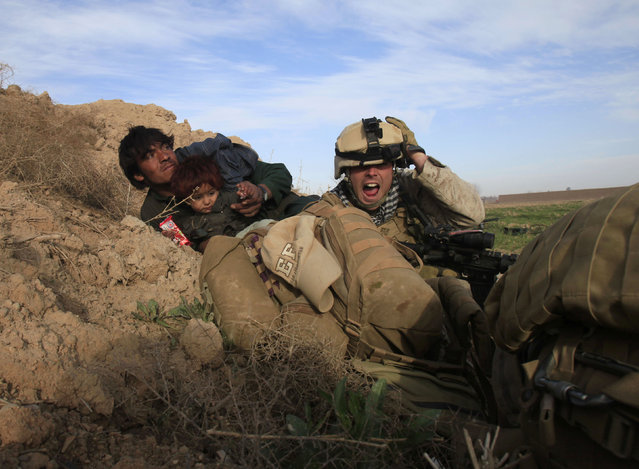 U.S. Marine Lance Corporal Chris Sanderson, 24, from Flemington, New Jersey shouts as he tries to protect an Afghan man and his child after Taliban fighters opened fire in the town of Marjah, in Nad Ali district, Helmand province, February 13, 2010. (Photo by Goran Tomasevic/Reuters)