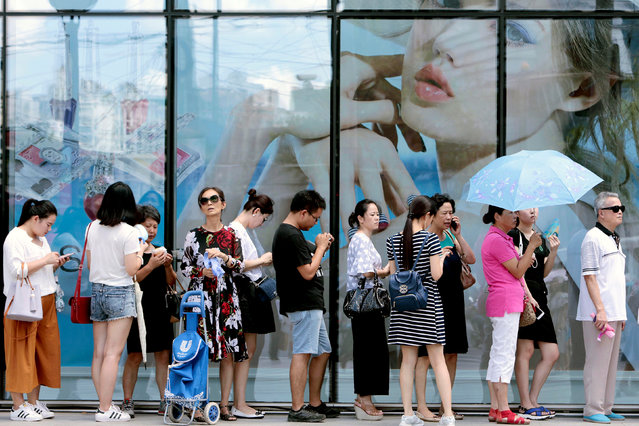 People queue outside of a newly opened duty free shop in Shanghai, China, August 8, 2016. (Photo by Reuters/China Daily)