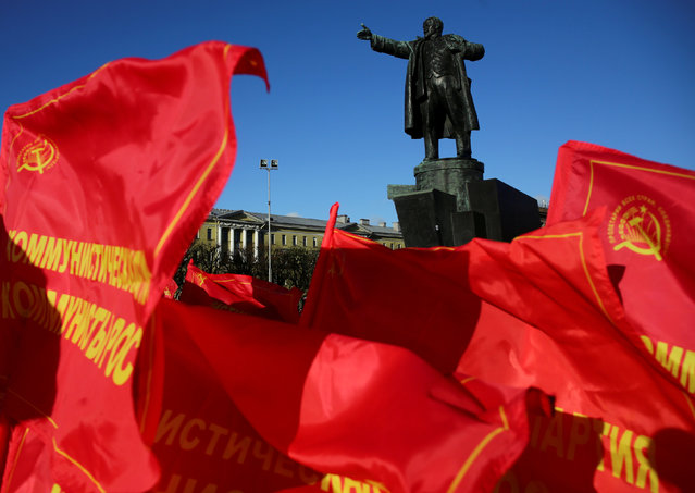Flags flutter in front of a monument to Soviet state founder Vladimir Lenin during a rally held by Russian Communist Party supporters to mark the Red October revolution's centenary in St. Petersburg, Russia November 7, 2017. (Photo by Anton Vaganov/Reuters)