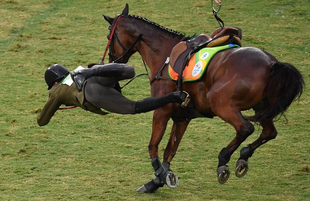 Lithuania's Justinas Kinderis is thrown from his horse in the show jumping portion of the men's modern pentathlon event at the Deodoro Stadium during the Rio 2016 Olympic Games in Rio de Janeiro on August 20, 2016. (Photo by Manan Vatsyayana/AFP Photo)