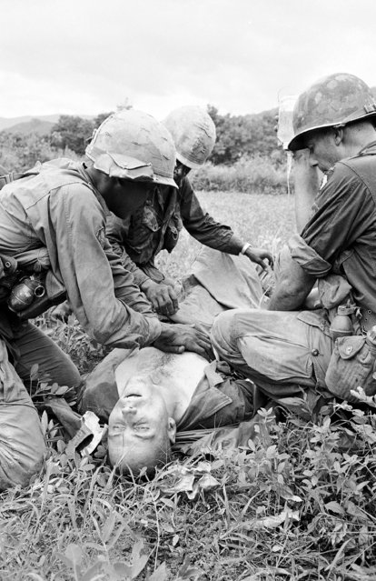 A medic gives blood transfusion to unidentified 101st airborne brigade soldier in futile effort to save his life at An Ninh, South Viet Nam on September 18, 1965. Victim was wounded when helicopters bringing in his unit for battle against Viet Cong were hit by heavy fire. The Americans were pinned down for 24 hours, preventing evacuation of casualties. This soldier died three hours after he was wounded. (Photo by AP Photo)