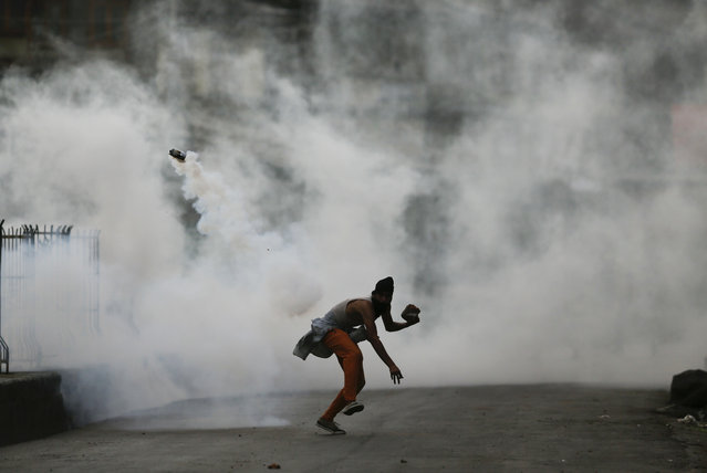 A Kashmiri protester throws a tear smoke shell on government forces as he reacts to the Sunday's killing of a young man in Srinagar, Indian controlled Kashmir, Monday, August 22, 2016. A security lockdown and protest strikes continued for the 45th straight day Monday, with tens of thousands of Indian armed police and paramilitary soldiers in full riot gear patrolling the tense region. The killing of a popular rebel commander on July 8 sparked some of Kashmir's largest protests against Indian rule in recent years. (Photo by Mukhtar Khan/AP Photo)