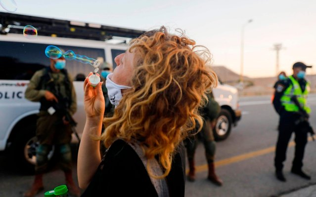 A peace activist blows bubbles during a protest against Israel's plans to annex parts of the occupied West Bank at the Almog junction, south of the West Bank city of Jericho, on June 27, 2020. (Photo by Ahmad Gharabli/AFP Photo)