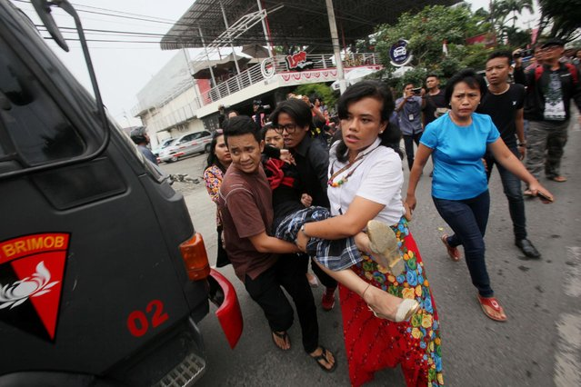 People carry an unconscious friend to an ambulance in front of a church after a would-be suicide bomber failed to detonate explosives during Sunday service in Medan, North Sumatra, Indonesia, Sunday, August 28, 2016. Police in the western Indonesian city said a would-be suicide bomber failed to detonate explosives in the packed church during Sunday mass. (Photo by Binsar Bakkara/AP Photo)