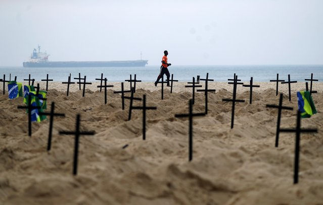 A man runs past the one hundred graves which were dug by activists of the NGO Rio de Paz on Copacabana beach symbolising the dead from the coronavirus disease (COVID-19), in Rio de Janeiro, Brazil, June 11, 2020. (Photo by Pilar Olivares/Reuters)