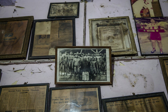 In this November 20, 2017 photo, photographs and certificates belonging to Indian Kushti wrestlers are displayed on the wall of Guru Hunuman Akhada, one of India's oldest akhada at Sabzi Mandi, in New Delhi, India. Like many traditions in rapidly modernizing India, kushti wrestling faces the threat of being left behind. But for many poor families, the ancient sport provides a glimmer of hope. (Photo by Dar Yasin/AP Photo)