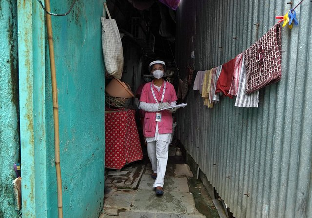 A health worker wearing protective face mask and face shield walks in an alley after checking the temperature of a resident at a slum during a checkup campaign for the coronavirus disease (COVID-19) in Mumbai, July 21, 2020. (Photo by Hemanshi Kamani/Reuters)