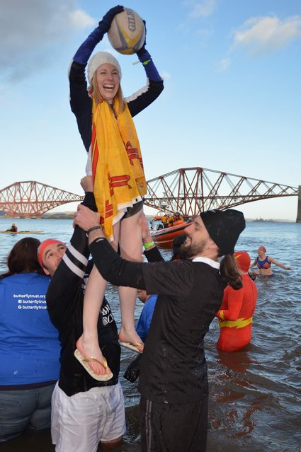 Two men lift a woman holding a rugby ball as they joined over 1,000 New Year swimmers, many in costume, braved freezing conditions in the River Forth in front of the Forth Rail Bridge during the annual Loony Dook Swim on January 1, 2013 in South Queensferry, Scotland. Thousands of people gathered last night to see in the New Year at Hogmanay celebrations in towns and cities across Scotland.  (Photo by Jeff J. Mitchell)