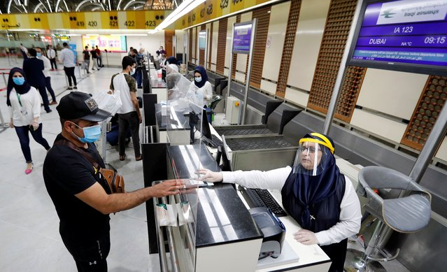 Passengers wearing protective masks check-in after the reopening of Baghdad International Airport, where flights halted due to the coronavirus disease (COVID-19) outbreak, in Baghdad, Iraq on July 23, 2020. (Photo by Thaier Al-Sudani/Reuters)
