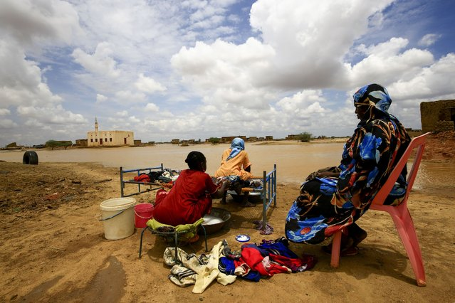 Sudanese women wash their clothes next to flood water, as a result of flooding and torrential rain, in the town of Osaylat, 50 km southeast of the capital Khartoum, on August 6, 2020, (Photo by Ashraf Shazly/AFP Photo)