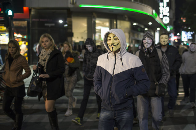 Protesters wearing Guy Fawkes masks walk along a street in downtown Belgrade November 5, 2014. (Photo by Marko Djurica/Reuters)