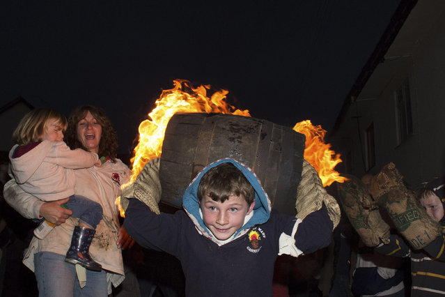 A boy runs with a burning barrel soaked in tar while attendees cheer him up in Ottery St. Mary November 5, 2014. (Photo by Daniel Leal-Olivas/Reuters)