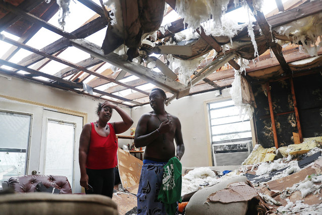 Latasha Myles and Howard Anderson stand in their living room where they were sitting when the roof blew off around 2:30am as Hurricane Laura passed through the area on August 27, 2020 in Lake Charles, Louisiana . The hurricane hit with powerful winds causing extensive damage to the city. (Photo by Joe Raedle/Getty Images)