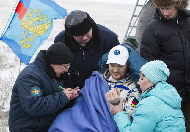 Ground personnel check International Space Station (ISS) crew member Alexander Gerst of Germany after a parachute landing in a Soyuz capsule in a remote area near the town of Arkalyk in northern Kazakhstan, November 10, 2014. (Photo by Shamil Zhumatov/Reuters)
