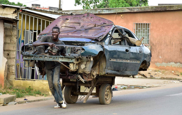 A man transports the carcass of a car on a two- wheeled carriage in a neighborhood in Abobo, a suburb of Abidjan, Côte d'Ivoire on December 1, 2017. (Photo by Issouf Sanogo/AFP Photo)