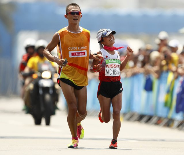 2016 Rio Paralympics, Athletics, Women's Marathon, T12, Fort Copacabana, Rio de Janeiro, Brazil on September 18, 2016. Misato Michishita of Japan crosses the finish line to win the silver medal while accompanied by her guide. (Photo by Jason Cairnduff/Reuters)