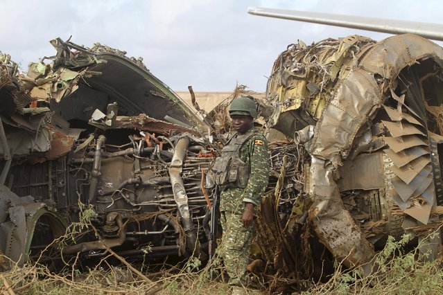 A Ugandan soldier serving in the African Union Mission in Somalia (AMISOM) stands guard as he secures the engine of a Tristar Air cargo plane that crash-landed in Arbiska outside Somalia's capital Mogadishu, October 13, 2015. (Photo by Feisal Omar/Reuters)