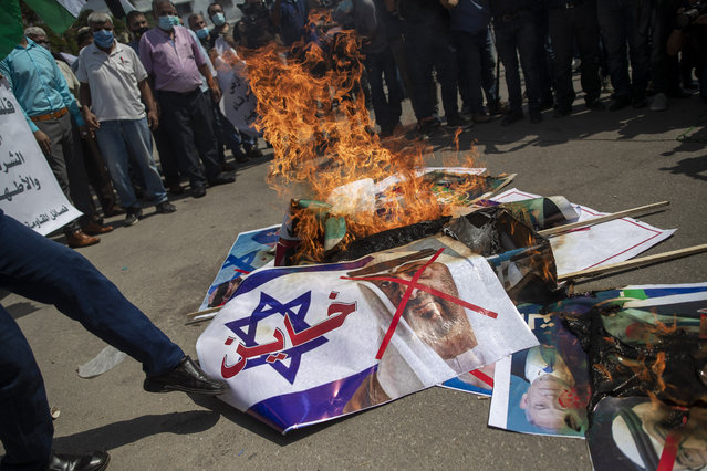 """Palestinians burn pictures of U.S. President Donald Trump, Israeli Prime Minister Benjamin Netanyahu, Bahrain's King Hamad bin Isa Al Khalifa and and Abu Dhabi Crown Prince Mohammed bin Zayed al-Nahyan, during a protest against the United Arab Emirates and Bahraini normalization agreement with Israel, in Gaza City, Tuesday, September 15, 2020. Israel is set to sign agreements with the UAE and Bahrain at the White House on Tuesday. Arabic on poster with representation of an Israeli flag reads, """"traitor"""". (Photo by Khalil Hamra/AP Photo)"""