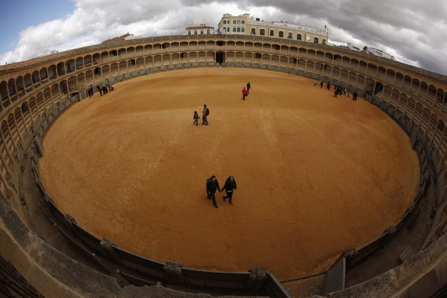 Tourists walk on the arena at the bullring in Ronda, near Malaga February 12, 2013. Ronda is considered one of the cradles of modern bullfighting emerged in the eighteenth century. Spain's parliament voted on Tuesday to consider protecting bullfighting as a national pastime, angering animal rights campaigners and politicians in two regions where the sport is banned. Picture taken with a fisheye lens. (Photo by Jon Nazca/Reuters)