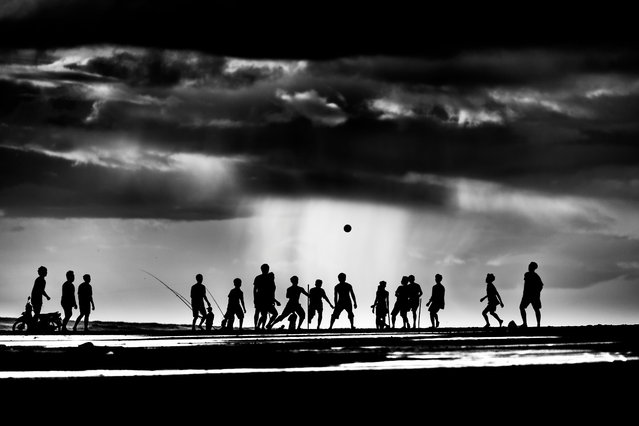 """Winner. """"Pekutatan beach, Bali. About an hour before sunset kids would gather to play football – and stay until dark. I photographed them over several days, hoping to get a nice sunset silhouette. That never came but there were glimpses of it and lots of storm clouds"""". MICK RYAN, JUDGE: """"If a photo is sometimes meant to tell a story, this has several chapters. A well-spotted scene by a photographer who was some distance away and taken with a telephoto lens that has compressed the action. I like the conversion to monotone, which with silhouettes can add more impact by its simplification"""". (Photo by Ian Webb/The Guardian)"""
