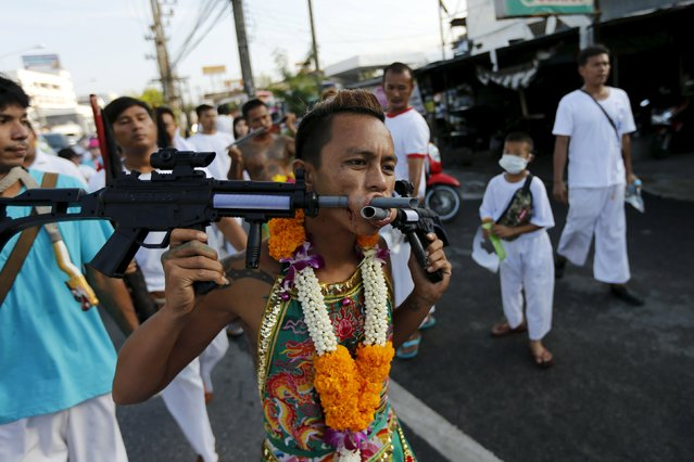 A devotee of the Chinese Ban Tha Rue shrine walks with guns pierced through his cheeks during a procession celebrating the annual vegetarian festival in Phuket, Thailand, October 17, 2015. (Photo by Jorge Silva/Reuters)