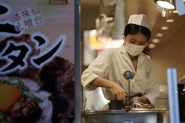 A restaurant employee wearing a face mask to help curb the spread of the coronavirus prepare a dish for a customer, Thursday, Septenber 10, 2020, in Tokyo. (Photo by Eugene Hoshiko/AP Photo)