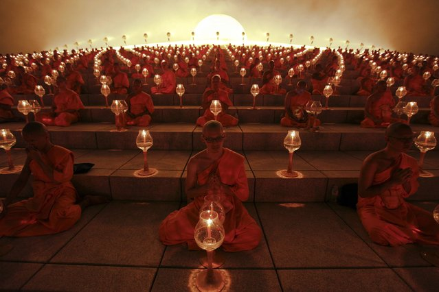 Buddhist monks pray at the Wat Phra Dhammakaya temple in Pathum Thani province, north of Bangkok on Makha Bucha Day February 25, 2013. Makha Bucha Day honours Buddha and his teachings, and falls on the full moon day of the third lunar month. (Photo by Kerek Wongsa/Reuters)