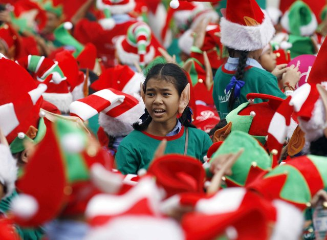 Students gather to break the Guinness World Record for the largest gathering of Christmas elves, outside a shopping mall in central Bangkok, November 25, 2014. As many as 1,792 of Santa's little helpers, aged between nine and 15, donned red, green and white hats, matching T-shirts and pointy plastic elf ears, as they formed up outside a shopping mall in Bangkok, the Thai capital. (Photo by Chaiwat Subprasom/Reuters)