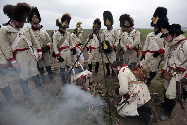 Historical re-enactment enthusiasts dressed as soldiers start a cooking fire near the southern Moravian village of Herspice November 28, 2014. (Photo by David W. Cerny/Reuters)