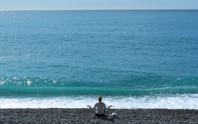 A woman gestures during a sun salutation, on the beach in Nice, southeastern France, Tuesday, March 19, 2013. (Photo by Lionel Cironneau/AP Photo)