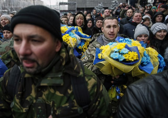 "Servicemen of ""Kiev 12"" military defence battalion sing a national anthem as they take part in a welcoming ceremony in central Ukrainian capital Kiev December 6, 2014. (Photo by Gleb Garanich/Reuters)"