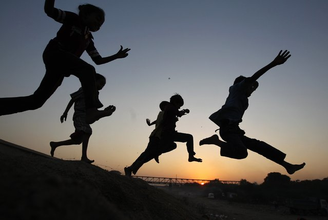 Children play on a sand dune as they are silhouetted against the setting sun in the western Indian city of Ahmedabad November 28, 2014. (Photo by Amit Dave/Reuters)