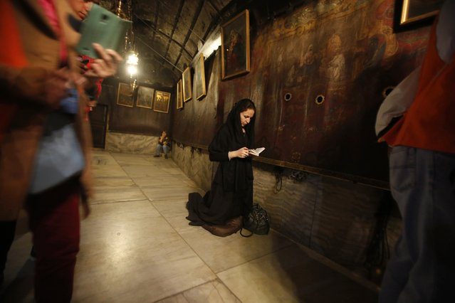 A Christian worshiper prays inside the cave, where Virgin Mary is believed to have given birth to Jesus, under the Church of Nativity in the West Bank city of Bethlehem December 6, 2014. (Photo by Mussa Qawasma/Reuters)