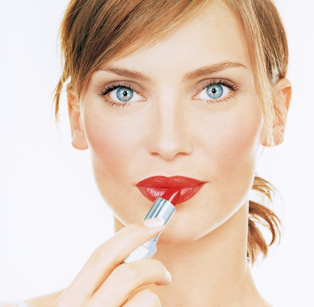 Woman applying lipstick. (Photo by Getty Images)