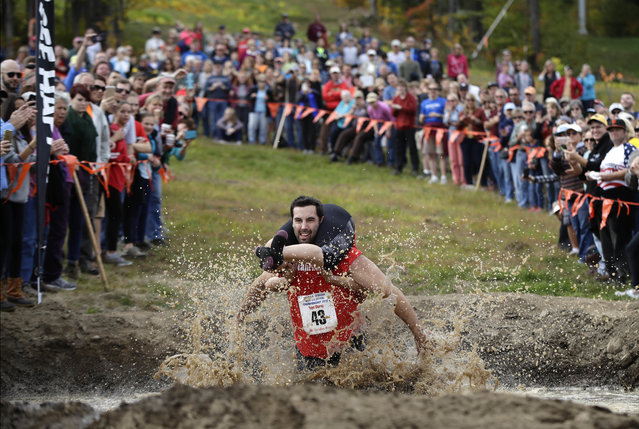 Elliot Storey races through the mud pit while carrying his wife, Giana Storey, both of Westbrook, Maine, to win the North American Wife Carrying Championship, Saturday, October 8, 2016, at the Sunday River Ski Resort in Newry, Maine. (Photo by Robert F. Bukaty/AP Photo)