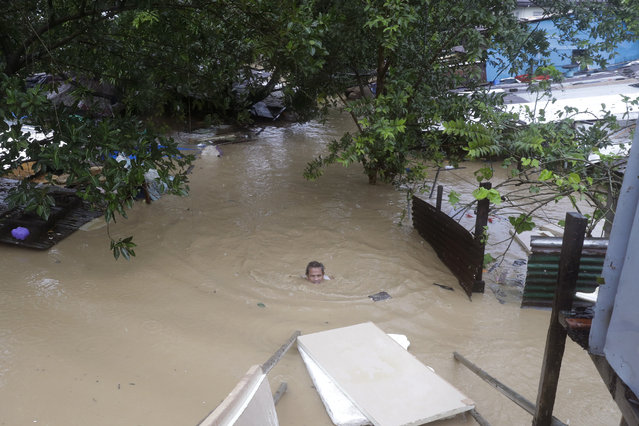 A man swims in neck deep floodwaters as it continues to rise in Marikina, Philippines, due to Typhoon Vamco on Thursday, November 12, 2020. (Photo by Aaron Favila/AP Photo)