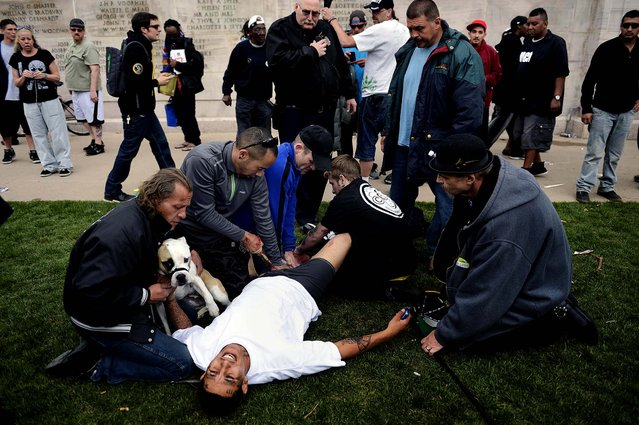 Denver Paramedics, Denver Police officers and good Samaritans  tend to a shooting victim at Civic Center Park after the 4/20 pot rally, Saturday, April 20, 2013 in Denver. Gunfire erupted at a Denver pot celebration Saturday, injuring two people and scattering a crowd of thousands who had gathered for the first 4/20 counterculture holiday since the state legalized marijuana. (Photo by Joe Amon/AP Photo/The Denver Post)