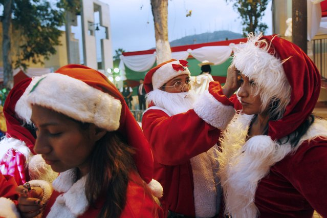 Inmates dressed as Santa Claus prepare to participate in an event ahead of Christmas celebrations at Santa Monica female prison in Lima December 19, 2014. (Photo by Enrique Castro-Mendivil/Reuters)