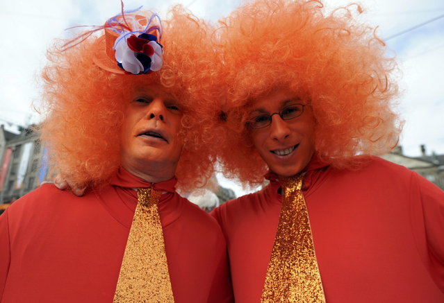 Two men wearing orange, the royal color, wait for Queen Beatrix's abdication ceremony in Amsterdam April 30, 2013. The Netherlands is celebrating Queen's Day on Tuesday, which also marks the abdication of Queen Beatrix and the investiture of her eldest son Willem-Alexander. (Photo by Laurent Dubrule/Reuters)