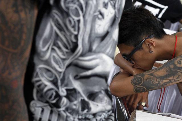 A young man gets a tattoo on her back during Bandung Body Art Festival at in Bandung, West Java, on December 7, 2014. (Photo by Rezza Estily/JG Photo)