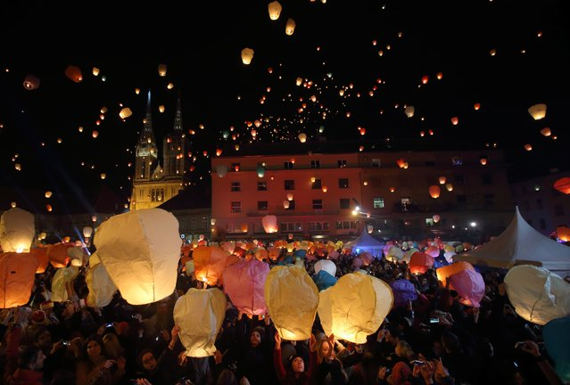 "Participants hold up sky lanterns to be released during the ""Kapulica & Lanterns"" event in Zagreb December 22, 2014. About 3000 participants attended the event, organized by contemporary artist Kresimir Tadija Kapulica as part of the ArtOmat Fair ahead of Christmas, which involved people releasing about a thousand lanterns to symbolize sending their wishes to the universe. (Photo by Antonio Bronic/Reuters)"