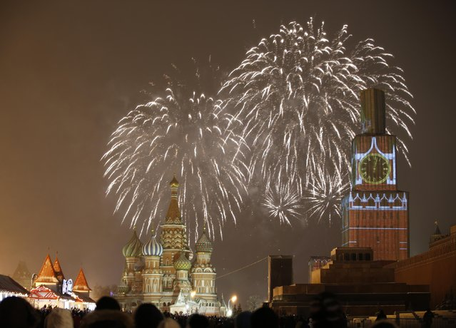 Fireworks light the sky over St. Basil's Cathedral and Kremlin's Spasskaya (Saviour) Tower, covered by scaffolding, during celebrations of New Year's Day in Red Square in Moscow January 1, 2015. (Photo by Tatyana Makeyeva/Reuters)