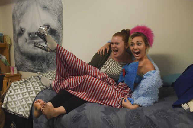 Katherine Quigley, 19, L, of Stuart's Draft, VA, poses for a picture with singer, songwriter, actress and philanthropist Miley Cyrus on the bed of Quigley's absent roommate as Cyrus makes a campaign visit for Hillary Clinton and Tim Kaine in Northern Virginia at George Mason University on Saturday, October 22, 2016 in Fairfax, VA. (Photo by Jahi Chikwendiu/The Washington Post)