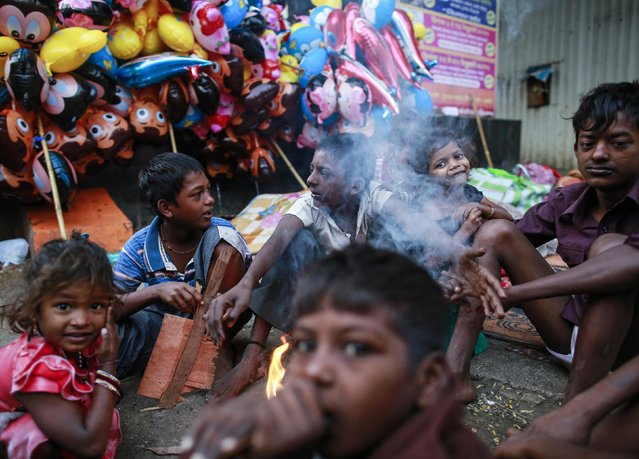 Children sit around a fire to keep themselves warm during the early morning hours along a road in Mumbai January 2, 2015. (Photo by Danish Siddiqui/Reuters)