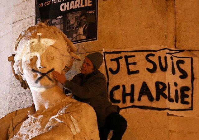 """A man touches the spray-painted shut mouth of a statue near a poster reading """"I am Charlie"""" as he takes part in a solidarity march (Marche Republicaine) in the streets of Paris January 11, 2015. (Photo by Charles Platiau/Reuters)"""