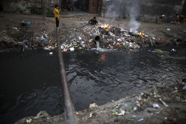 A girl stands on a pipe beside an open sewer in a slum on the outskirts of Lahore January 12, 2015. (Photo by Zohra Bensemra/Reuters)