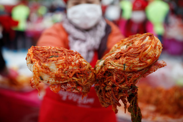 A woman poses for photographs with traditional side dish Kimchi during the Seoul Kimchi Festival in central Seoul, South Korea, November 4, 2016. (Photo by Kim Hong-Ji/Reuters)