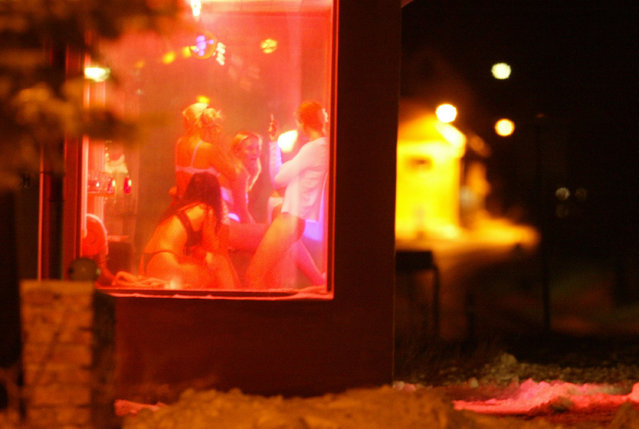 KRIMOV, CZECH REPUBLIC - DECEMBER 16: Prostitutes lounge in the display window of a roadside brothel December 16, 2003 near Krimov, Czech Republic near the German border. Prostitution is big business in the Czech Republic along the border areas with Germany and Austria.  (Photo Sean Gallup/Getty Images)