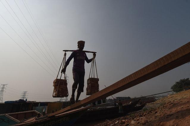 A worker unloads construction materials from a cargo ship in Dhaka on December 28, 2020. (Photo by Munir Uz Zaman/AFP Photo)
